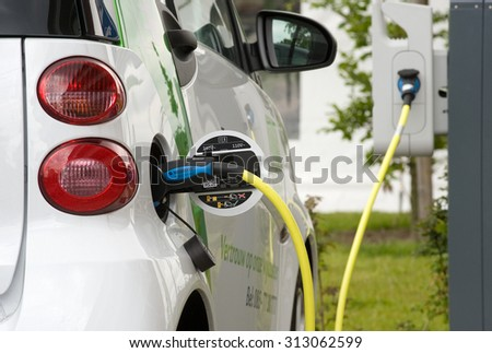 ENSCHEDE, THE NETHERLANDS - JUNE 02, 2015: An electric car is parked at a parking spot and is being recharged at a power station.