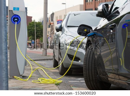 ENSCHEDE, THE NETHERLANDS - SEPT 08: Two electric cars are parked at a parking spot in the center of a town while they are being recharged at a power station, September 08, 2013 in the Netherlands.