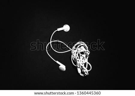 Entangled White Telephone Earphones isolated on Black Background