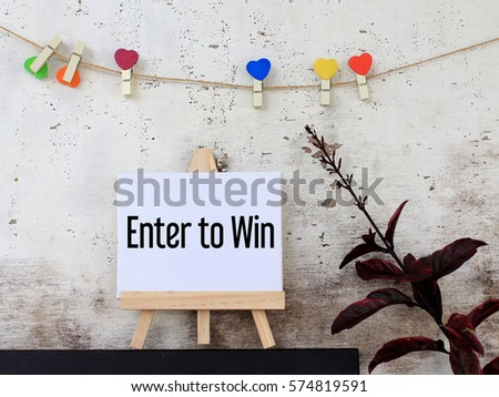 Enter to win - business concept words on canvas stand. rustic wooden background