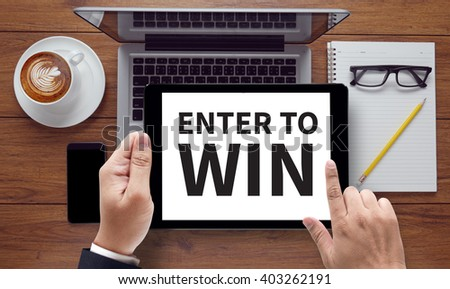 ENTER TO WIN , on the tablet pc screen held by businessman hands - online, top view #403262191