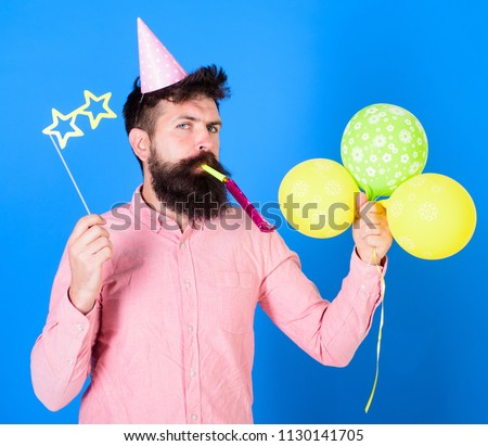 Entertainer with colorful baloons at kids party, international childrens day. Bearded artist with party wistle and paper star shaped glasses wearing birthday cap. Bearded man on blue background.