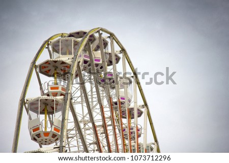 Entertainment industry for sunday holiday rides. Painted Ferris wheel for citizens and guests, big wheel metal construction