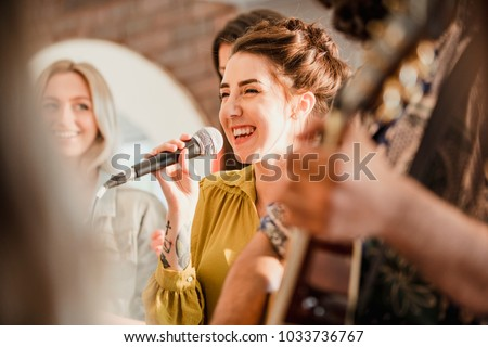 Entertianment at a wedding. A female singer is interacting with the crowd while a man plays an acoustic guitar.  #1033736767