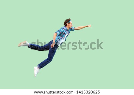 Enthusiasm concept. Full length profile side view of young man in casual style felt himself a superhero or super man and flying. indoor studio shot, isolated on green background.