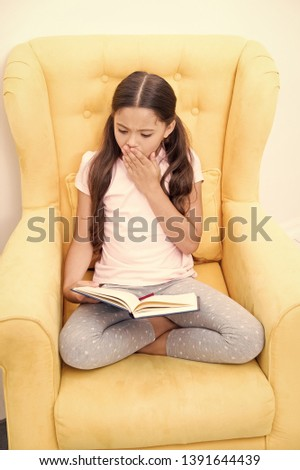 Enthusiastic about exciting story. Reading hobby. Girl child sit yellow armchair read book. Kid cute bookworm. Girl kid cute pajamas relax read fairytale book before sleep. Encourage useful habits.
