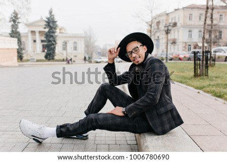 Enthusiastic african guy in white sneakers sitting on the road. Outdoor portrait of black young man in sport shoes chilling on the street.