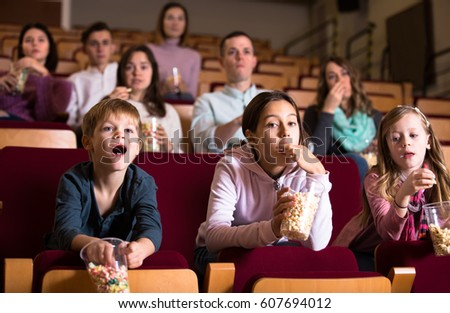 Enthusiastic audience attending movie night with popcorn in cinema house #607694012