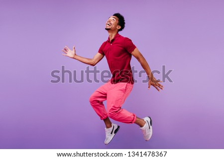 Enthusiastic black man posing emotionally on purple backgrond. Indoor photo of good-looking african guy in sport shoes jumping in studio.