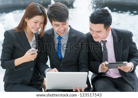 Enthusiastic business people communicating via different gadgets