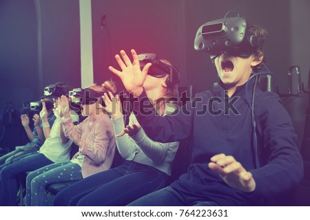 Enthusiastic  cheerful positive  children in virtual reality glasses in quest room
