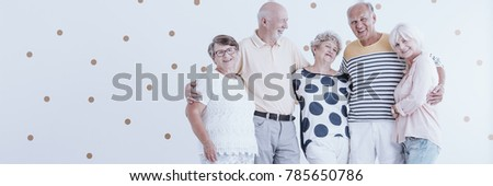 Enthusiastic elderly friends celebrating their meeting against white wallpaper with gold dots