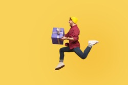 Enthusiastic extremely joyful hipster guy running quickly fast with gift box, flying in air holding birthday present surprise, hurry to give holiday bonus. full length studio shot isolated on yellow
