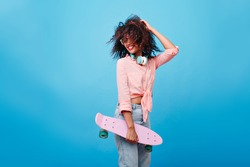 Enthusiastic girl with brown curly hairstyle enjoying photoshoot on blue background. Slim african girl with skateboard playing with her hair and laughing in studio.