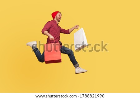Enthusiastic joyful hipster trendy guy running in air with shopping bags in hands, hurrying to catch sale, flying and rushing for thrift discount. full length studio shot isolated on yellow background Stockfoto ©