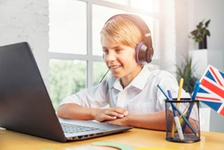 Enthusiastic kid in headphones studying English online