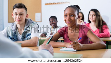 Enthusiastic positive  girls and boys taking the notes while teacher giving a class