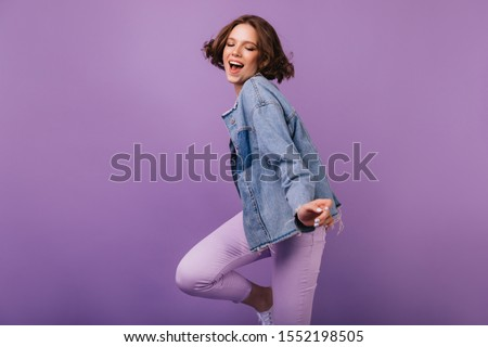Enthusiastic white girl in oversize jacket dancing with pleasure. Indoor photo of adorable pretty woman with short hair.