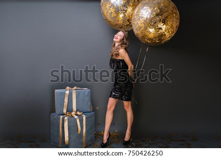 Enthusiastic white girl with sparkle helium balloons enjoying  birthday photoshoot on dark background. Adorable female model in black dress posing in studio with big present boxes and smiling.