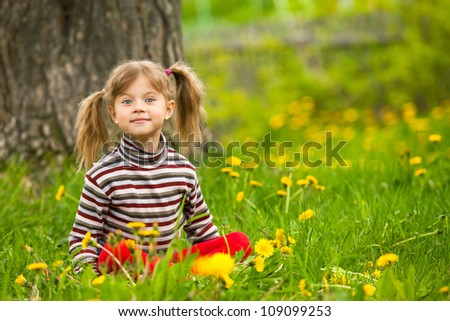 Enthusiastically surprised lovely little five-year girl sitting in grass
