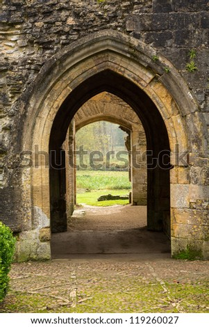 Entrance arches of Minster Lovell in Cotswold village with graveyard