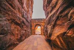 Entrance archway for Shivalaya in Badami, Karnataka, INDIA.  Passage way through rock cliffs.