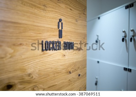 Entrance door to a men locker room in the gym.Spa,swimming pool,gym locker room door with caption sign and little grey lockers in the background.Sportsmen locker room.Sport changing room