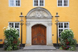 Entrance doorway of the Old City Hall. Beautiful historic yellow painted building with a wooden door in the city center, Aalborg, Denmark.