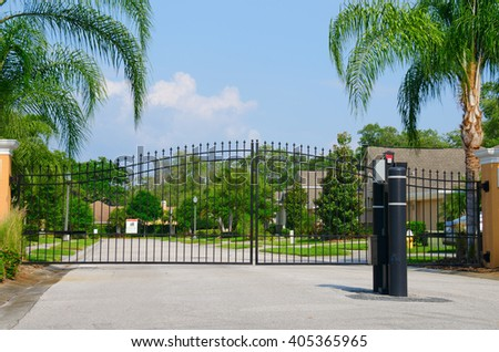 Entrance gate to a beautiful gated residential house community with lush green trees and grass #405365965