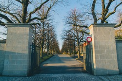 Entrance gate to the Bois-de-vaux cemetery in Lausanne, Switzerland during winter time and in the evening hours. Romantic but scary cemetery in Lausanne