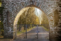 Entrance gate with stone facade and a path to a cemetery