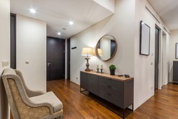 Entrance hall in the bright luxury apartment. Hallway dresser with lamp