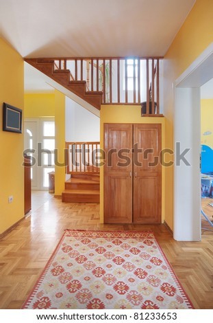 Entrance hall of a modern house, view on rooms and wooden stairs.