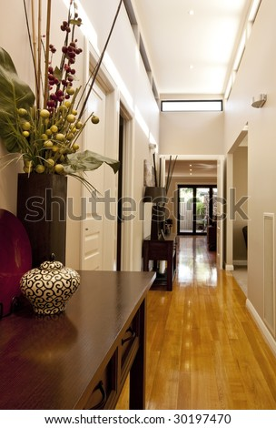 Entrance hall of new showcase home, with polished floorboards and elegant decor.