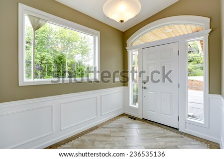 Entrance hallway with tile floor and beige wall with white trim. White door with arch and windows