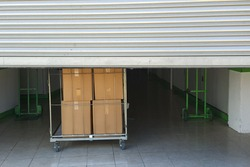 Entrance into self storage units, big cart with carton boxes in front, metal gate
