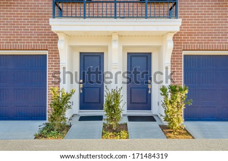 Entrance of a house. Double door with two garage doors.