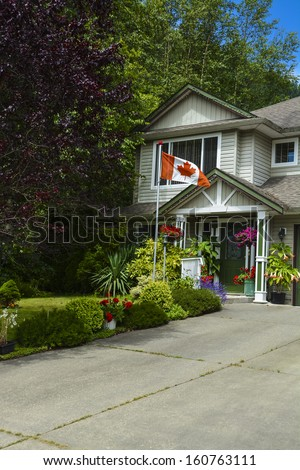 Entrance of a house with Canadian flag on front yard  in British Columbia, Canada. Entrance of a house with concrete driveway.