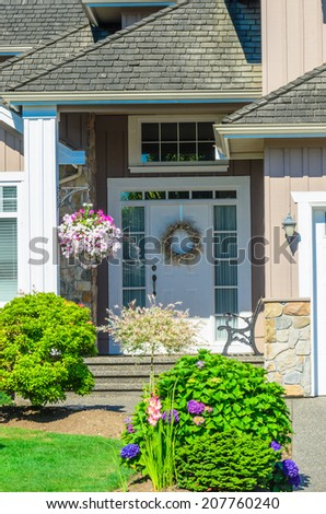 Entrance of a house with nicely trimmed and landscaped front yard.