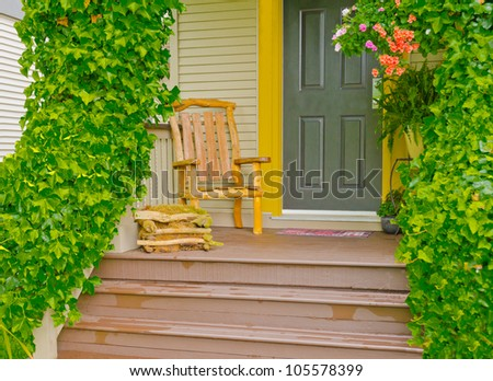 Entrance of a house with the hand made wooden chair on the porch and ivy on the rails