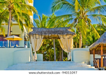 Entrance of a luxury resort with two people having their breakfast at the terrace. - stock photo