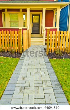 Entrance of a nice house with path and wooden fence