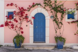 Entrance of a typical Greek home in Assos, with arched stone work, pink painted walls and blue door with a decorative pot plant, flowering bougainvillea tree with red flowers