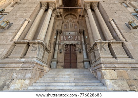 Entrance of al Rifai Mosque with closed decorated wooden doors, ornate columns, ornate recessed stone wall and stairs, Old Cairo, Egypt #776828683