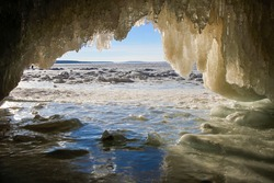 Entrance of ice cave with icicles framing frozen Lake Superior on Apostle Islands, Wisconsin