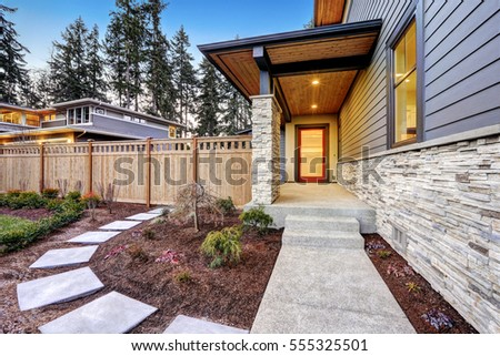 Entrance of  Luxurious new construction home with blue siding and stone decor. Concrete walkway lead to long covered porch with modern glossy front door. Northwest, USA #555325501