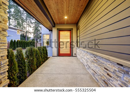 Entrance of  Luxurious new construction home with long covered porch that features plank ceiling, natural stone wall design and modern glossy front door. Northwest, USA #555325504