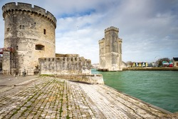 Entrance of the old harbor of La Rochelle in France, with the Tour de la Chaine at the foreground and Tour Saint-Nicolas at the background, Nouvelle Aquitaine region, department of Charente-Maritime