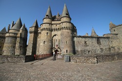 entrance of Vitre castle and Vitre town hall with drawbridge, walls and pointed towers at sunny day with blue sky