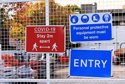 Entrance to a construction site with warning signs attached to a fence. Covid 19 stay 2 metres apart. Personal protective equipment must be worn. Entry.